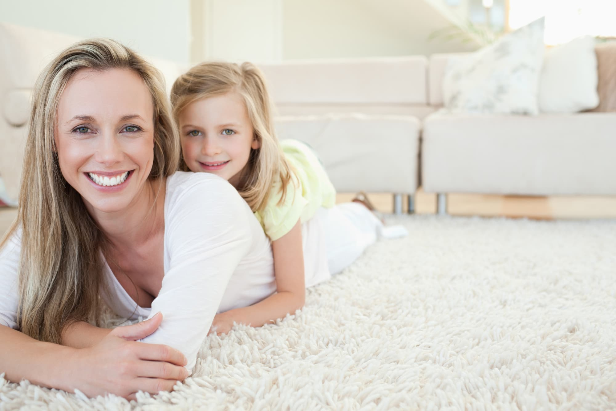mother and daughter laying on clean white carpet